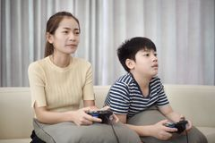 Asian woman with asian boy playing video games at home. Asian women with asian boy playing video games at home Stock Image