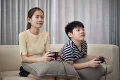 Asian woman with asian boy playing video games at home. Asian women with asian boy playing video games at home Royalty Free Stock Photos