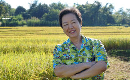 Asian woman in bright shirt at her SME farmland. Abstract own ag Royalty Free Stock Image