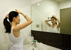 Asian woman brushing hair in front of mirror in bathroom stock photo