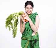 Asian woman with a bunch of carrots Royalty Free Stock Photo