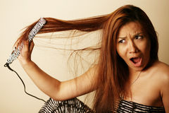 Asian woman burning her hair Royalty Free Stock Photography