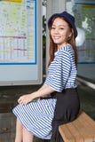 Asian woman at bus stop stock photography