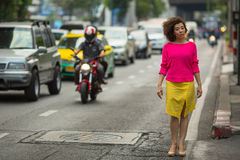 Asian woman on a busy highway. Stock Image