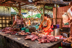 Asian woman butcher sells meat Stock Images