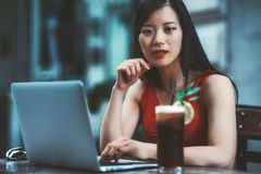 Asian woman in cafe with netbook and beverage. The portrait of a young charming Asian woman with a laptop and a glass of a cool mint drink on the table in front stock images