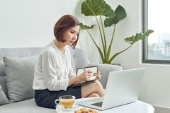Asian woman in cafe using laptop and note some data on notepad.  stock photos