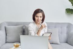 Asian woman in cafe using laptop and note some data on notepad.  royalty free stock photos