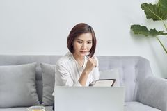 Asian woman in cafe using laptop and note some data on notepad.  royalty free stock image