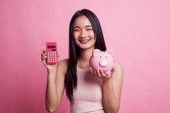 Asian woman with calculator and piggy bank. Royalty Free Stock Image