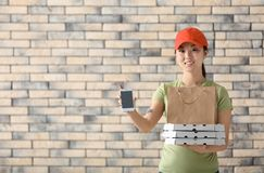 Asian woman with cardboard pizza boxes, paper bag and mobile phone on brick wall background. Food delivery service stock image