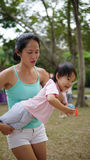 Asian woman carrying toddler in family games outdoor Stock Photo