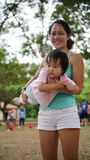 Asian woman carrying toddler and participating in family games Royalty Free Stock Images