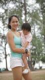 Asian woman carrying toddler Stock Image