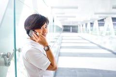 Asian woman on cellphone on skybridge Stock Photography