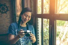 Asian woman checking and reviewing photos in digital camera near Stock Images