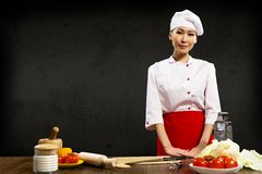 Asian woman chef. Standing near a kitchen table, ready for lunch royalty free stock image