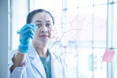 Asian woman chemical scientist write formular on glass board royalty free stock photo