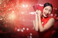 Asian woman in cheongsam dress holding angpao Stock Photography