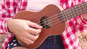 Asian woman child playing ukulele. In the park stock video footage
