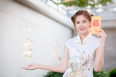 The Asian woman in chinese dress holding couplet 'Happy' (Chine Stock Photo