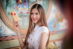The Asian woman in chinese dress holding couplet 'Happy' (Chine. Asian woman in chinese dress holding couplet 'Happy ' (Chinese word) with chinese temple royalty free stock image