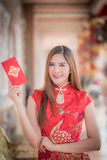 Asian woman in chinese dress holding couplet 'Happy' (Chinese w Royalty Free Stock Image