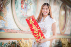 The Asian woman in chinese dress holding couplet 'Lucrative' (C. Asian woman in chinese dress holding couplet 'Lucrative ' (Chinese word) with chinese temple stock photo