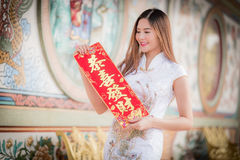 The Asian woman in chinese dress holding couplet 'Lucrative' (C. Asian woman in chinese dress holding couplet 'Lucrative ' (Chinese word) with chinese temple stock photography
