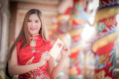 The Asian woman in chinese dress holding couplet 'Lucrative' (C. Asian woman in chinese dress holding couplet 'Lucrative ' (Chinese word) with chinese temple royalty free stock photo