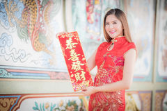 The Asian woman in chinese dress holding couplet'strong' (Chin. Asian woman in chinese dress holding couplet 'Lucrative ' (Chinese word) with chinese temple stock photo