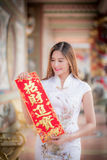 Asian woman in chinese dress holding couplet'strong' (Chinese. Asian woman in chinese dress holding couplet'strong ' (Chinese word) with chinese temple royalty free stock photo