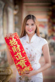 Asian woman in chinese dress holding couplet'strong' (Chinese. Asian woman in chinese dress holding couplet'strong ' (Chinese word) with chinese temple stock photography