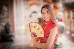 The Asian woman in chinese dress holding couplet'success' (Chin. Asian woman in chinese dress holding couplet'success' (Chinese word) with chinese temple stock photography