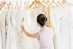 Asian woman choose long White dresses from wardrobe. In Wedding Shop royalty free stock photography
