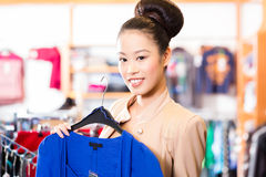 Asian Woman choosing clothes in fashion shop Royalty Free Stock Photography