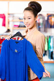 Asian Woman choosing clothes in fashion shop Royalty Free Stock Images