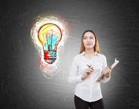 Asian woman with clipboard and a light bulb Royalty Free Stock Photos