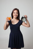 Asian woman with a clock drink orange juice. Royalty Free Stock Photos