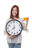 Asian woman with a clock drink orange juice. Royalty Free Stock Photography