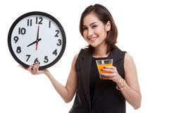 Asian woman with a clock drink orange juice. Royalty Free Stock Image