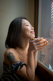 Asian woman close eyes feels positive with orange cup. Beautiful smiling asian woman close eyes early morning alone feels positive with orange cup between hands Royalty Free Stock Photo