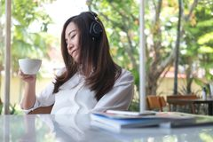 Asian woman close her eyes and listening to music with headphone while drinking coffee with feeling happy and relax in cafe with g Stock Photo