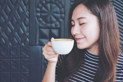 Asian woman close her eyes smelling and drinking hot coffee with feeling good in cafe Stock Image