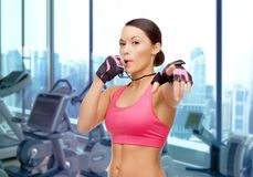 Asian woman coach blowing whistle over gym. People, sport, fitness and healthy lifestyle concept - asian woman coach blowing whistle over gym machines background royalty free stock image
