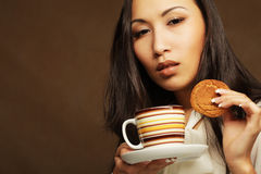 Asian woman with coffee and cookies. Royalty Free Stock Photos