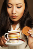 Asian woman with coffee and cookies. Young asian woman with coffee and cookies royalty free stock images