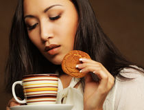 Asian woman with coffee and cookies. Stock Image