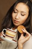 Asian woman with coffee and cookies. Stock Photo