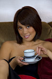 Asian woman with coffee cup. Young beautiful asian woman with brunette hair and brown eyes smiling and holding coffee cup and saucer while sitting on sofa Royalty Free Stock Image